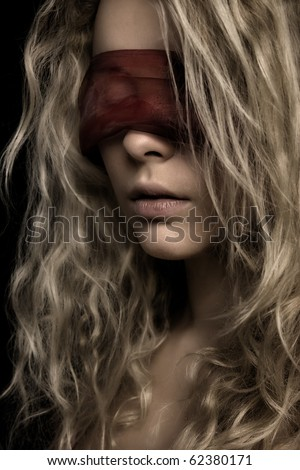 Mysterious beautiful face with ribbon on eyes - stock photo