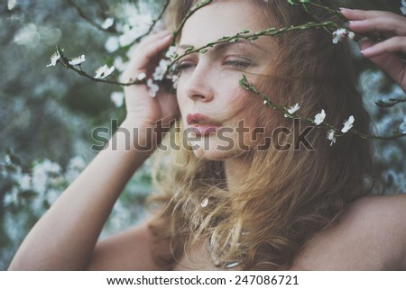 mysterious beautiful girl with flowers in her hair. Queen blooming gardens. Fields of flowers - stock photo