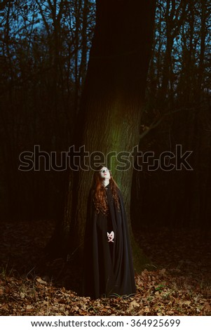 Mysterious black robed woman in the forest at night . Dark and fantasy