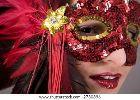 mysterious brunette wearing carnival red mask on her face