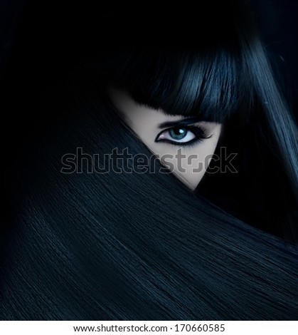 mysterious brunette with hair covered face and aquamarine eyes - stock photo