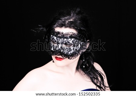 Mysterious brunette woman in mask with ruby lips on black background