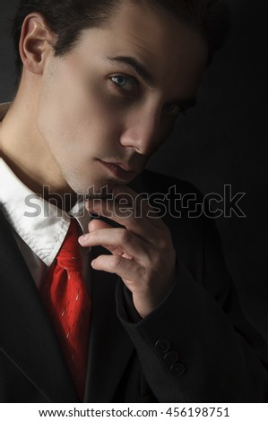 mysterious business man in suit with red tie on black background - stock photo