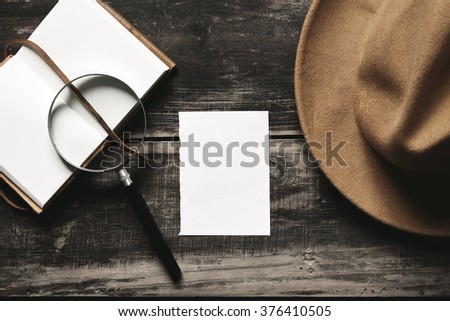 Mysterious detective game concept. Opened notebook in leather cover, sheet of white paper, felt brown hat and big vintage magnifier steel glasses isolated on black aged wood table. Top view. - stock photo