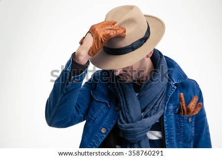 Mysterious fashion man in jeans jacket, scarf, hat and brown leather gloves posing over white background - stock photo
