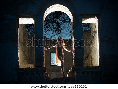 Mysterious female figure in the arc of the ruined building  - stock photo