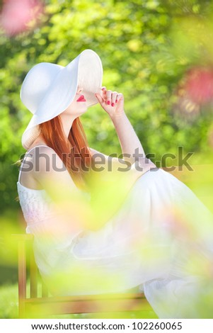 Mysterious girl in a garden - stock photo