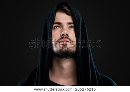 Mysterious man. Handsome young man in black hood looking up while standing against black background