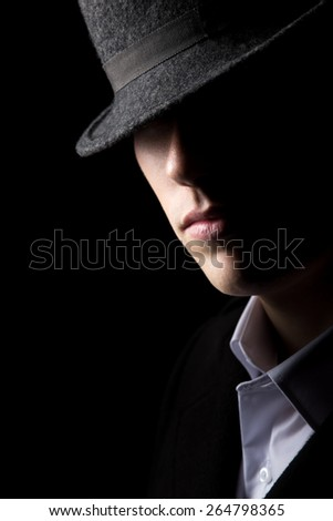 Mysterious man in hat with half of his face in the shadows, minimalistic studio shot against black background, low key lighting - stock photo