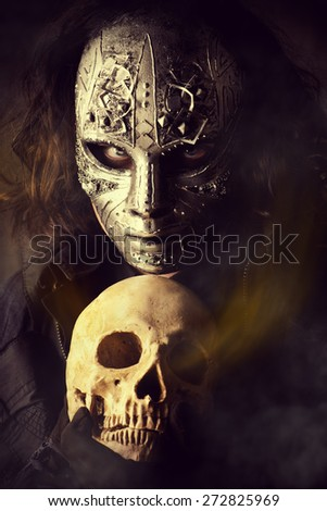 Mysterious man in iron mask holding skull. Steampunk. Fantasy. Halloween. - stock photo
