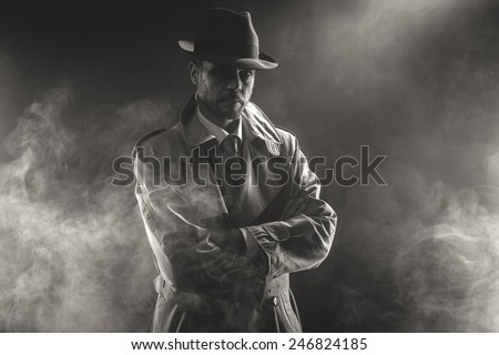 Mysterious man waiting with arms crossed in the fog, 1950s style film noir - stock photo