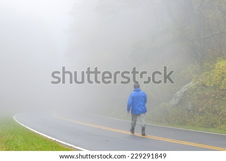 Mysterious man walks into foggy forest road  - stock photo