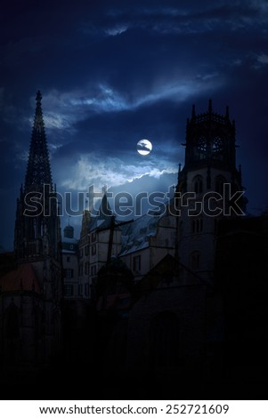 Mysterious medieval castle and the cathedral church at night on a background of the full moon - stock photo