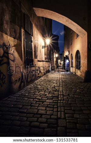 mysterious narrow alley with lanterns in Prague at night - stock photo
