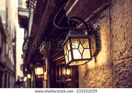 mysterious narrow alley with lanterns in Venice at evening, Italy - stock photo