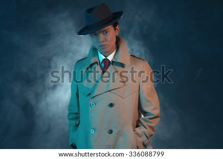 Mysterious retro 1940 asian gangster fashion man in raincoat. - stock photo