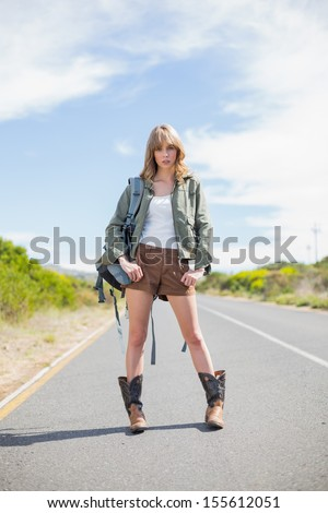 Mysterious sexy blonde posing while hitchhiking on a deserted road in summertime - stock photo