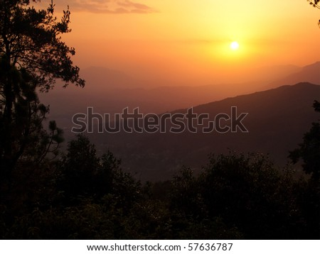 Mysterious sunset over landscape with hills and mountains
