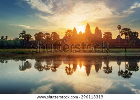 Mysterious towers of ancient temple complex Angkor Wat at sunrise. Siem Reap, Cambodia. Temple Mountain and the sun reflected in lake at dawn. Angkor Wat is a popular tourist attraction. - stock photo