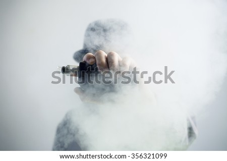 Mysterious vaping man wearing a hat, holding up a mod, obscured behind a cloud of vapor.  - stock photo