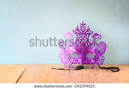 Mysterious Venetian masquerade mask on wooden table  - stock photo