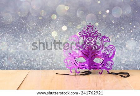 Mysterious Venetian masquerade mask on wooden table and glitter background  - stock photo