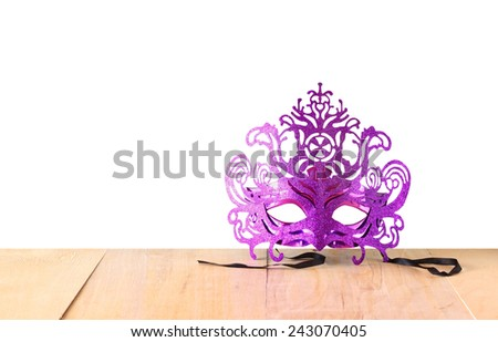 Mysterious Venetian masquerade mask on wooden table with isolated backgroun  - stock photo