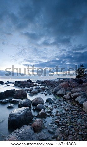 Mysterious view of stones and pebbles in water after sunset. - stock photo