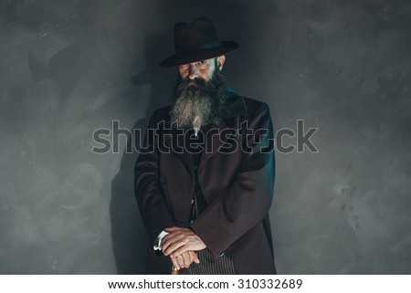 Mysterious vintage beard man in 1900 style fashion with cane against grey wall. - stock photo