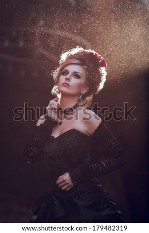 Mysterious woman dressed in gothic dress posing in ruined building - stock photo