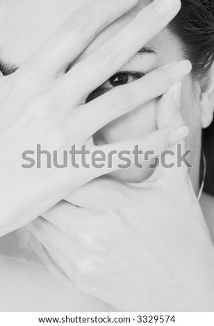Mysterious woman holding hands in front of her face - stock photo