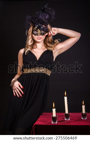 Mysterious woman in a mask near the table with alight candles over black background - stock photo