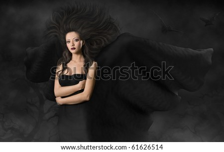 Mysterious woman in black dress and flying wings and hairs. gothic style make up