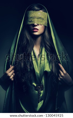 mysterious woman in green bandage on eyes - stock photo