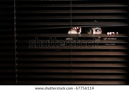 Mysterious woman pulls the blinds apart to see the outside world - stock photo