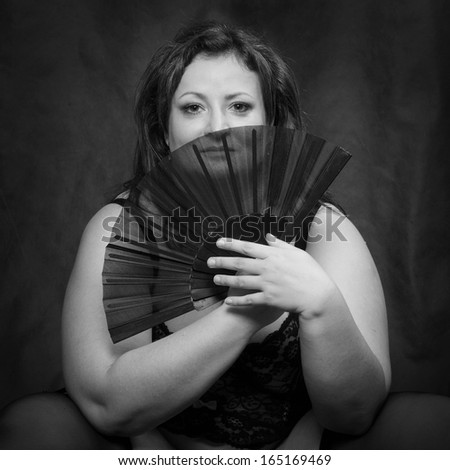 Mysterious woman with folding fan. Black and white photography. - stock photo