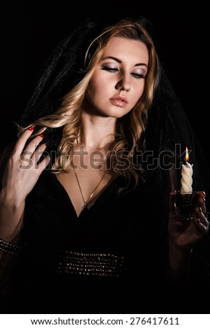 Mysterious young woman with a candle in darkness - stock photo