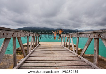 MYSTERY ISLAND, VANUATU - FEBRUARY 15, 2014: A young couple from a cruise ship cool off in the beautiful waters of Mystery Island. - stock photo