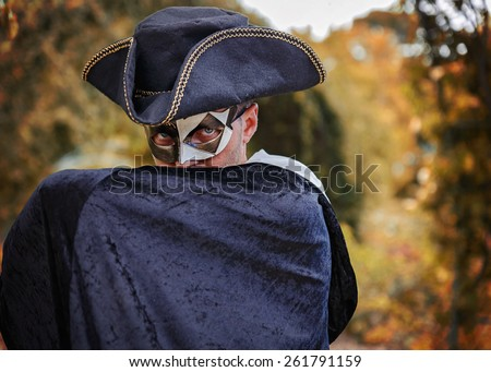 Mystery man in masquerade mask, triangle hat and black velvet cape hiding his lower face with his hand. Autumn (fall) forest background, shallow depth of field - stock photo