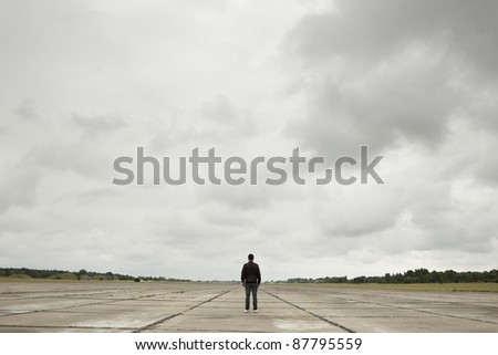 Mystery man in the midle of the old runway. - stock photo