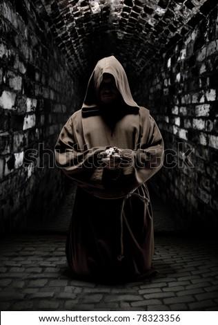 Mystery monk praying on kneels in dark temple corridor - stock photo