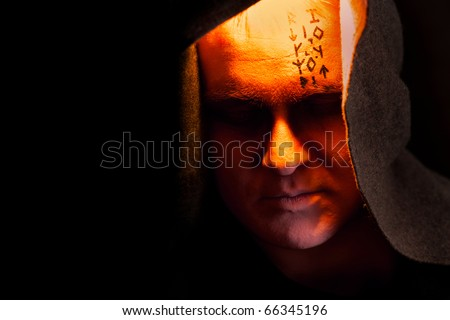Mystery monk with the runes on the face. Portrait in the shadows. - stock photo