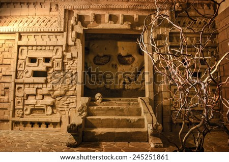 Mystery of Aztec temple. Image of ancient temple stylization depicting scull facade and steps surrounded by stone walls and vine - stock photo