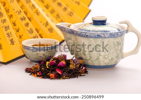Mystery of tea ceremony. Closeup image of the heap of colored tealeaves placed in front of traditional crockery and Chinese hand fan with hieroglyphs isolated on white background