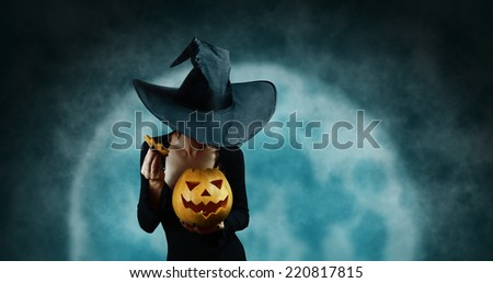 Mystery witch opening Halloween carved pumpkin on full moon background. Halloween, horror theme - stock photo
