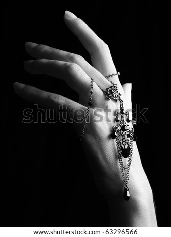 mystic black & white female hand with gothic chain - stock photo