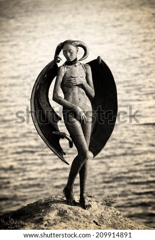 Mystic creature - woman in body paint with wings and horns - stock photo