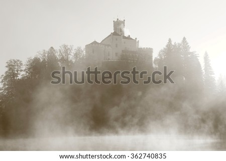 Mystic foggy castle on the hill - stock photo