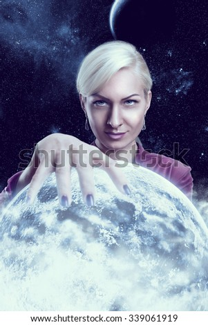 Mystic fortune teller woman holding a planet ball in the night - stock photo