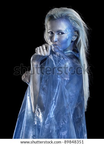 mystic mermaid theme showing a blond bodypainted woman coated with translucent blue fabrics, studio photography in black back - stock photo